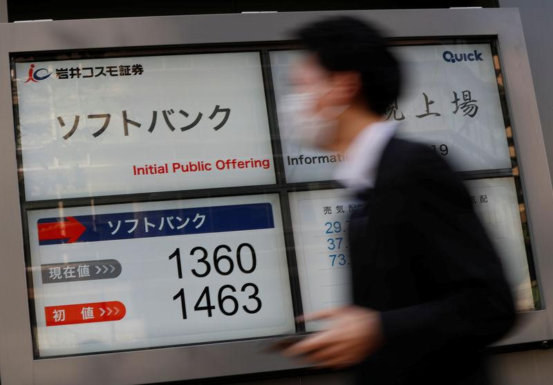 A man walks past in front of a stock quotation board showing the price of the SoftBank Corp. on the Tokyo Stock Exchange outside a brokerage in Tokyo, Japan December 19, 2018. REUTERS/Issei Kato