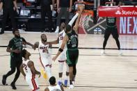 Boston Celtics' Jaylen Brown (7), Miami Heat's Jimmy Butler (22) and Jae Crowder (99) look on as Bam Adebayo (13) blocks a shot attempt by the Celtics' Jayson Tatum (0) in the closing seconds of overtime of an NBA conference final playoff basketball game, Tuesday, Sept. 15, 2020, in Lake Buena Vista, Fla. (AP Photo/Mark J. Terrill)