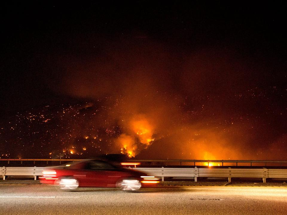 A vehicle passes by the burning Route fire, a brush wildfire off Interstate 5 north of Castaic, Calif., Saturday, Sept. 11, 2021.