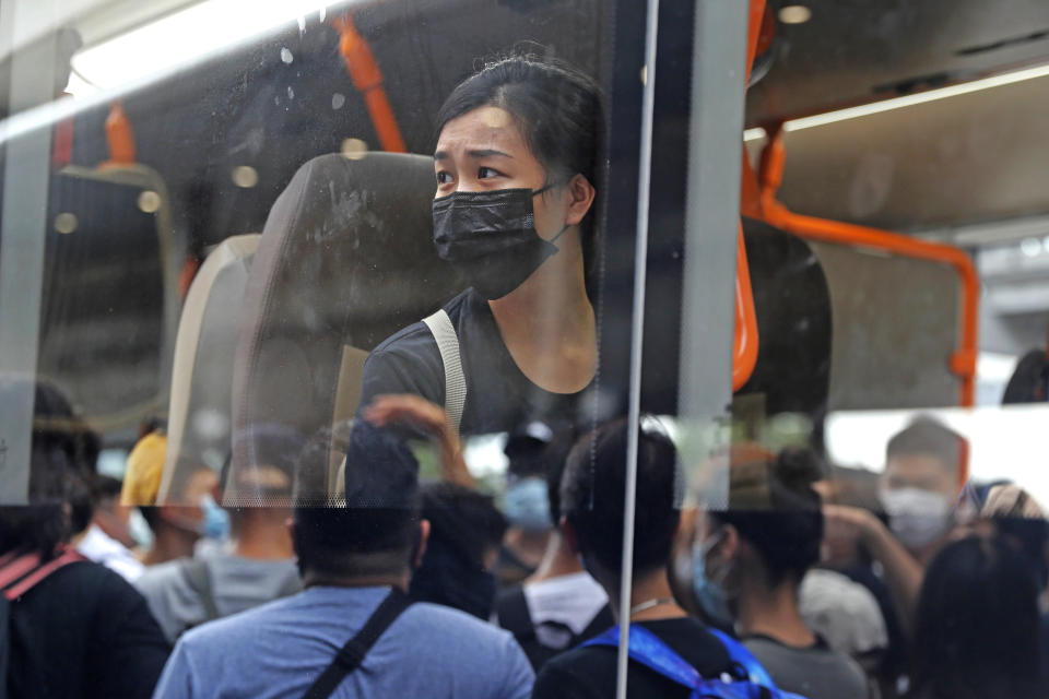 A pro-democracy protestor looks at the other protesters from a bus outside the airport in Hong Kong, Sunday, Sept. 1, 2019. Train service to Hong Kong's airport was suspended Sunday as pro-democracy demonstrators gathered there, while protesters outside the British Consulate called on London to grant citizenship to people born in the former colony before its return to China. (AP Photo/Kin Cheung)