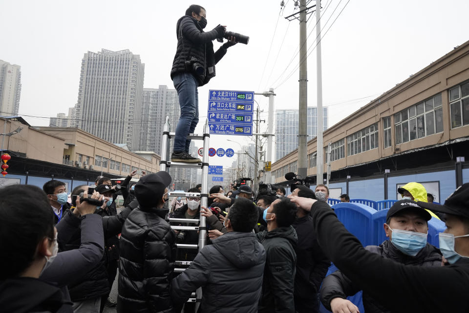 A photographer on a tall ladder tries to shoot photos of the World Health Organization convoy after it entered the the Huanan Seafood Market on the third day of a field visit in Wuhan in central China's Hubei province on Sunday, Jan. 31, 2021. Scientists initially suspected the coronavirus came from wild animals sold in the market. The market has since been largely ruled out but for the visiting WHO team of international researchers it could still provide hints to how the virus spread so widely. (AP Photo/Ng Han Guan)
