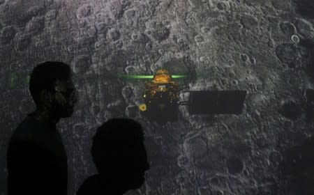 Student walk past a screen during a live streaming of Chandrayaan-2 landing at an educational institute in Mumbai