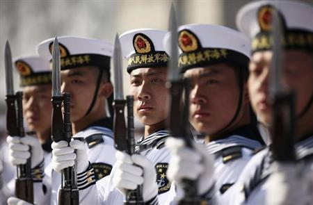 New recruits of the Chinese Navy fleet stand with their guns during the parade marking the end of their first training session in Qingdao