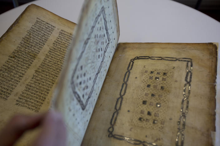 """In this photo taken Sunday, Oct. 5, 2014, a library official shows a Jewish manuscript smuggled into Israel from Damascus in a Mossad spy operation in the early 1990s in Jerusalem. The manuscript is one of the earliest existing complete manuscripts of the Hebrew bible. The Jerusalem District Court ruled Monday, Aug. 17, 2020 that the books were """"treasures of the Jewish people"""" that had """"historic, religious and national importance"""" and must be preserved. It determined that the best way to do so would be to keep them at the National Library under a public trust. (AP Photo/Sebastian Scheiner)"""