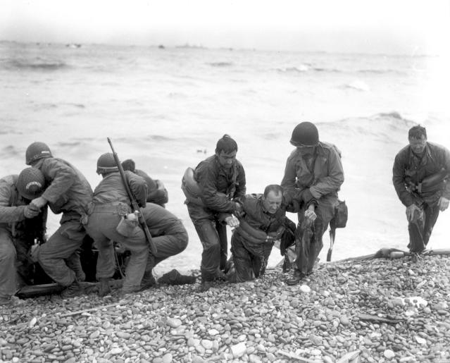 <p>Members of an American landing party assist troops whose landing craft was sunk by enemy fire off Omaha Beach, near Colleville-sur-Mer, France, on June 6, 1944. (Photo: Weintraub/U.S. National Archives/handout via Reuters) </p>