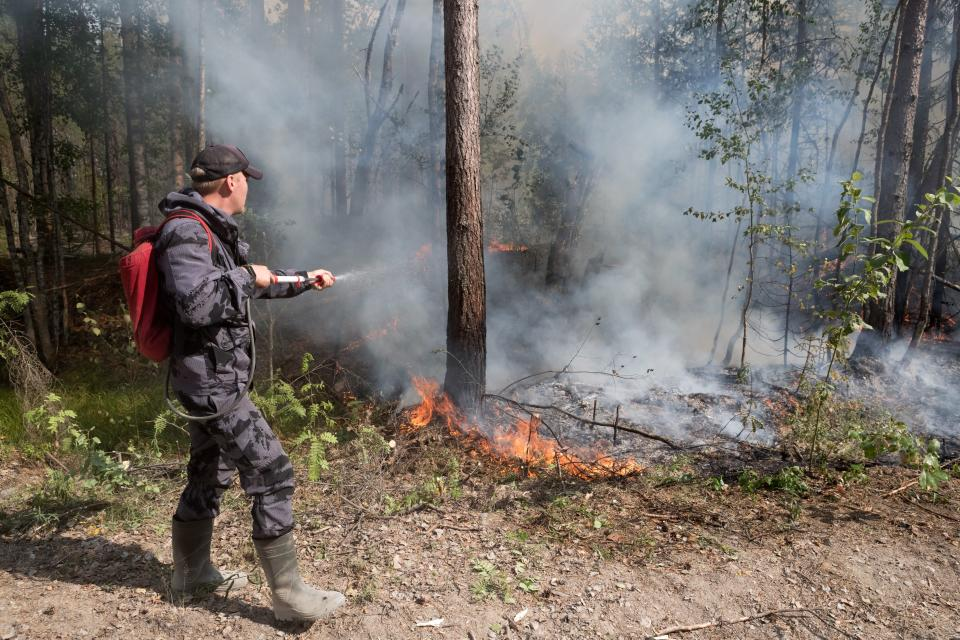 A firefighting crew mops up spot fires near the Syamozero Lake in Pryazhinsky District of the Republic of Karelia, about 700 km.(438 miles) south-west of Moscow, Russia on Wednesday, July 21, 2021. Volunteers have helped in Karelia as well. Anna Gorbunova, coordinator with the Society of Volunteer Forest Firefighters that focuses on the Ladoga Skerries national park in Karelia, told The Associated Press last week that the blazes there this year are the biggest since 2008. (AP Photo/Ilya Timin)
