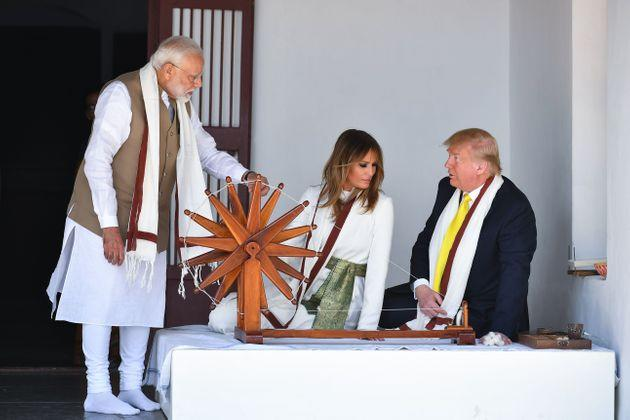 US President Donald Trump and First Lady Melania Trump listen to Prime Minister Narendra Modi (L) as they sit next to a charkha, or spinning wheel, during their visit at Gandhi Ashram in Ahmedabad on February 24, 2020.