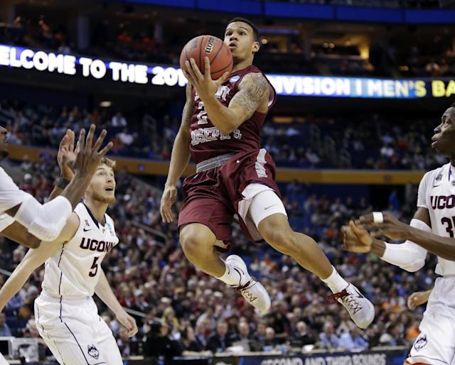 Saint Joseph's Chris Wilson, center, drives past Connecticut's Niels Giffey, left, during the first half of a second-round game in the NCAA college basketball tournament in Buffalo, N.Y., Thursday, March 20, 2014. (AP Photo/Nick LoVerde)