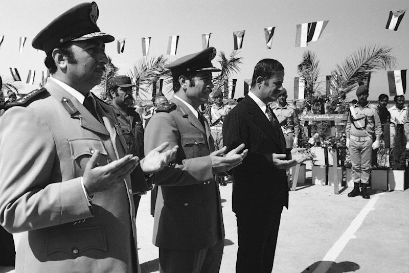 FILE - In this Sunday, Oct. 6, 1974 file photo, Syrian President Hafez Assad, right, and Gen. Mustafa Tlass, war minister, center, take part in ceremonies in Damascus honoring Syrian dead on the first anniversary of the last war with Israel. All others are unidentified. A top general who has abandoned President Bashar Assad's regime was a longtime friend from Syria's most powerful Sunni family, and his break with the inner circle signals crumbling support from a privileged elite. Brig. Gen. Manaf Tlass was a commander in the powerful Republican Guard and the son of former defense minister Mustafa Tlass, who held the post for 32 years until he retired in 2004.(AP Photo, File)