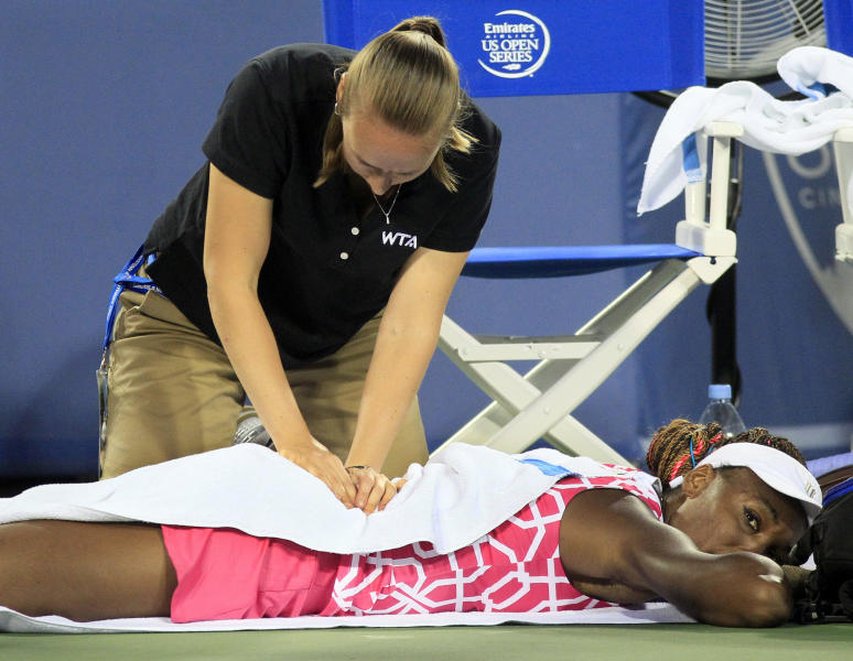 Venus Williams has her back worked on by a trainer during a semifinals match against Li Na, from China, at the Western & Southern Open tennis tournament, Saturday, Aug. 18, 2012, in Mason, Ohio. (AP Photo/Al Behrman)