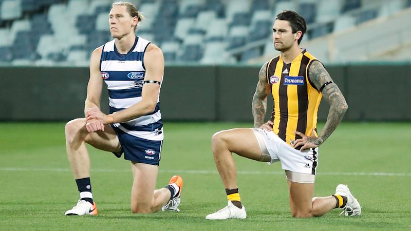 Mark Blicavs and Chad Wingard take a knee before Geelong's clash with Hawthorn. (Photo by Michael Willson/AFL Photos via Getty Images)