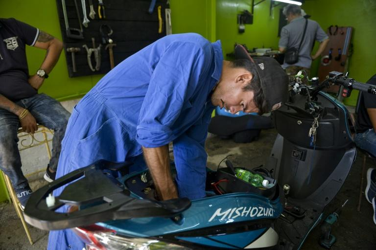 Mechanics have work to do servicing Cuba's fleet of electric motorcycles (AFP Photo/YAMIL LAGE)