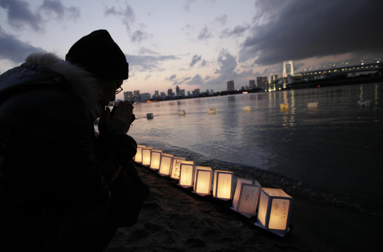 A man prays beside lanterns placed at the waterfront in Tokyo Bay to mark the first anniversary of the earthquake and tsunami which devastated northeast Japan, in Tokyo, Sunday, March 11, 2012. People across Japan prayed and stood in silence on Sunday to remember the massive disaster that struck the nation one year ago, killing just over 19,000 people and unleashing the world's worst nuclear crisis in a quarter century. (AP Photo/Greg Baker)