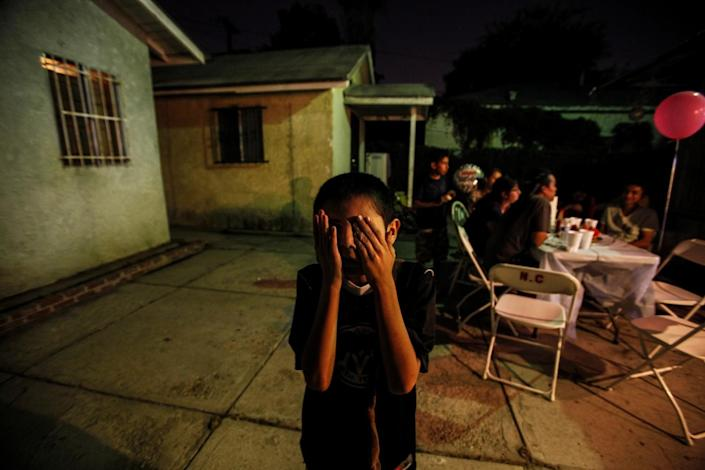 Jese Castillo, 11, covers his eyes as he plays during his 11th birthday party in his back yard, in South Los Angeles.