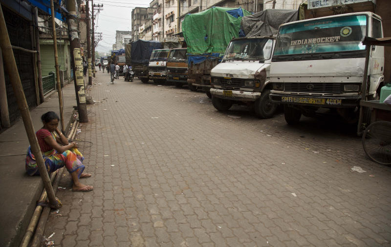 FILE - In this Monday, Sept. 10, 2018 file photo, a laborer sits near trucks at a closed market during a day-long strike to protest rising fuel prices among other economy issues, in Gauhati, India. Even proponents of carbon taxes acknowledge that an increase in fuel taxes can disproportionally hurt low-income people. Energy costs make up a larger portion of their overall expenses, so a fuel price increase eats up more of their paycheck and leaves with less to spend. (AP Photo/Anupam Nath)