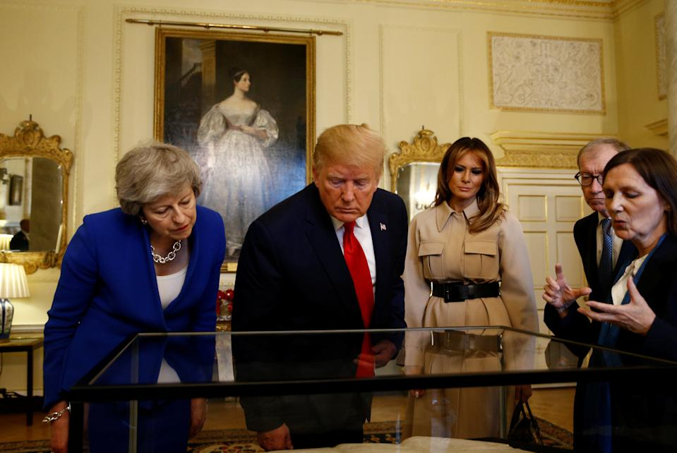 Prime Minister Theresa May (left) with US President Donald Trump and first lady Melania Trump view a historical document in Downing Street, London, on the second day of his state visit to the UK.