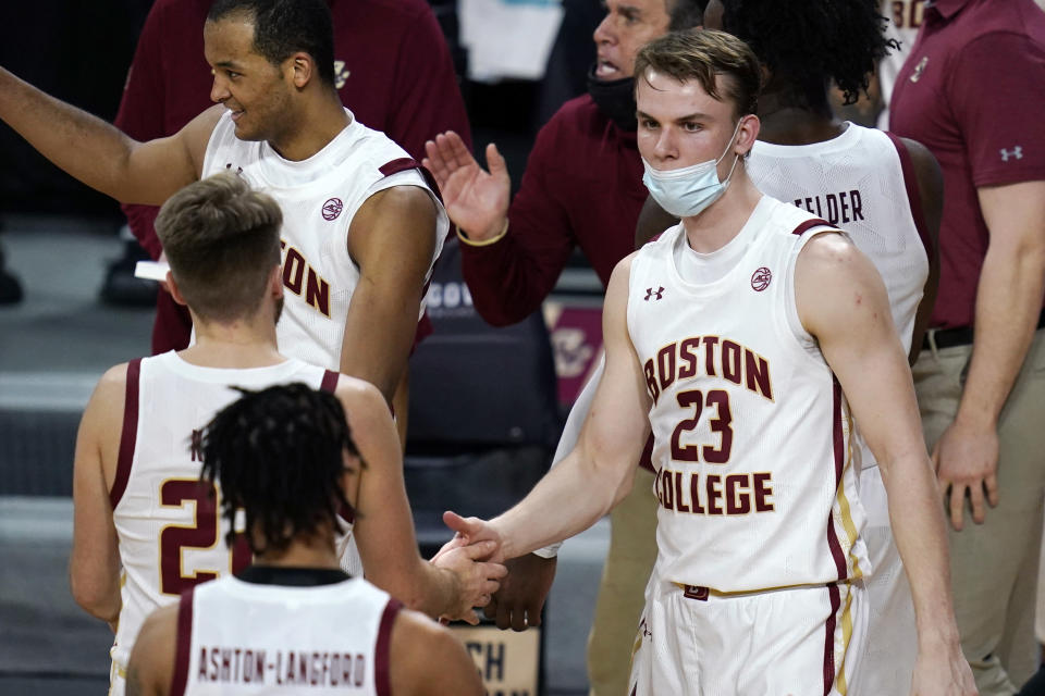Boston College forward Andrew Kenny (23), who joined the team as a walk-on, congratulates teammates during the second half of an NCAA college basketball game against Wake Forest, Wednesday, Feb. 10, 2021, in Boston. With COVID-19 protocols limiting Boston College to six scholarship players for its games against North Carolina State and Wake Forest, the Eagles relied on walk-ons to fill out their bench. Kenny had two rebounds in the six minutes he played against Wake Forest. (AP Photo/Charles Krupa)