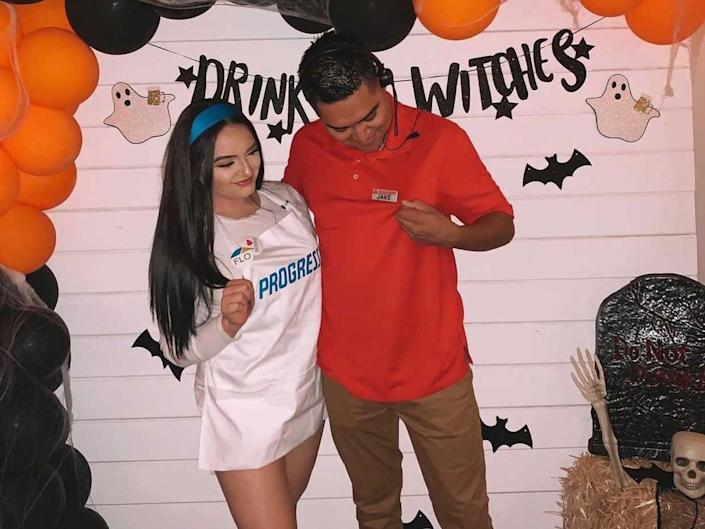 A couple dressed as Flo from Progressive and Jake from State Farm pose in front of a black and orange balloon wall.
