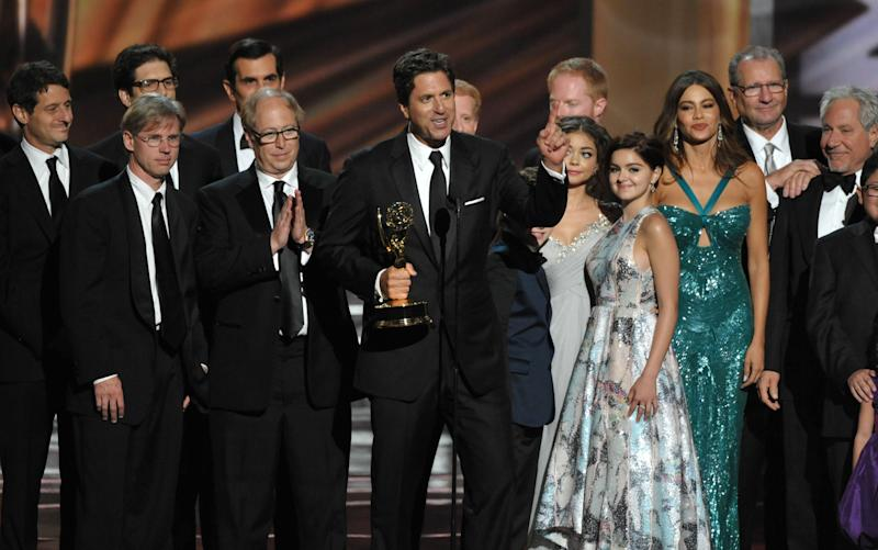"Steven Levitan, center, and the cast and crew of ""Modern Family"" accept the outstanding comedy series award at the 64th Primetime Emmy Awards at the Nokia Theatre on Sunday, Sept. 23, 2012, in Los Angeles. (Photo by John Shearer/Invision/AP)"