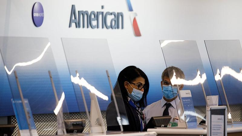 Employees wear protective masks behind plastic shielding in the American Airlines check-in counter area at O'Hare International Airport (ORD) in Chicago, Illinois