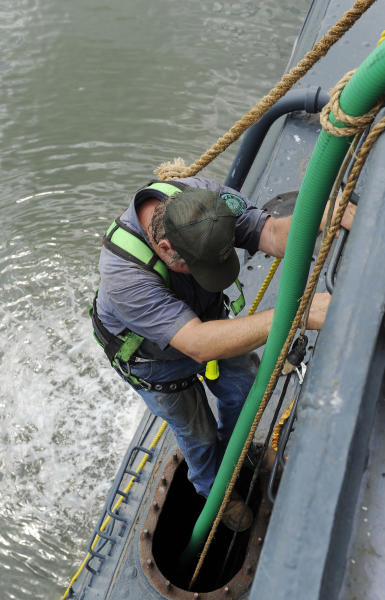 Norman Snipe climbs down into a tank on the port side of the USS Texas to reposition a pump hose Wednesday, June 13, 2012, in Houston. The 100-year-old battleship's hull sprung a leak five days ago and has been taking on as much as 1,000 gallons of seawater every minute as workers struggle to contain it. (AP Photo/Pat Sullivan)