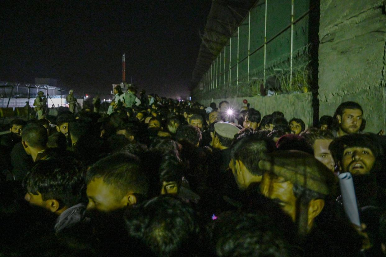 In this picture taken in the late hours on August 22, 2021 Afghans wait outside the foreign military-controlled part of the airport in Kabul, hoping to flee the country following the Taliban's military takeover of Afghanistan. (Photo by WAKIL KOHSAR / AFP) (Photo by WAKIL KOHSAR/AFP via Getty Images)
