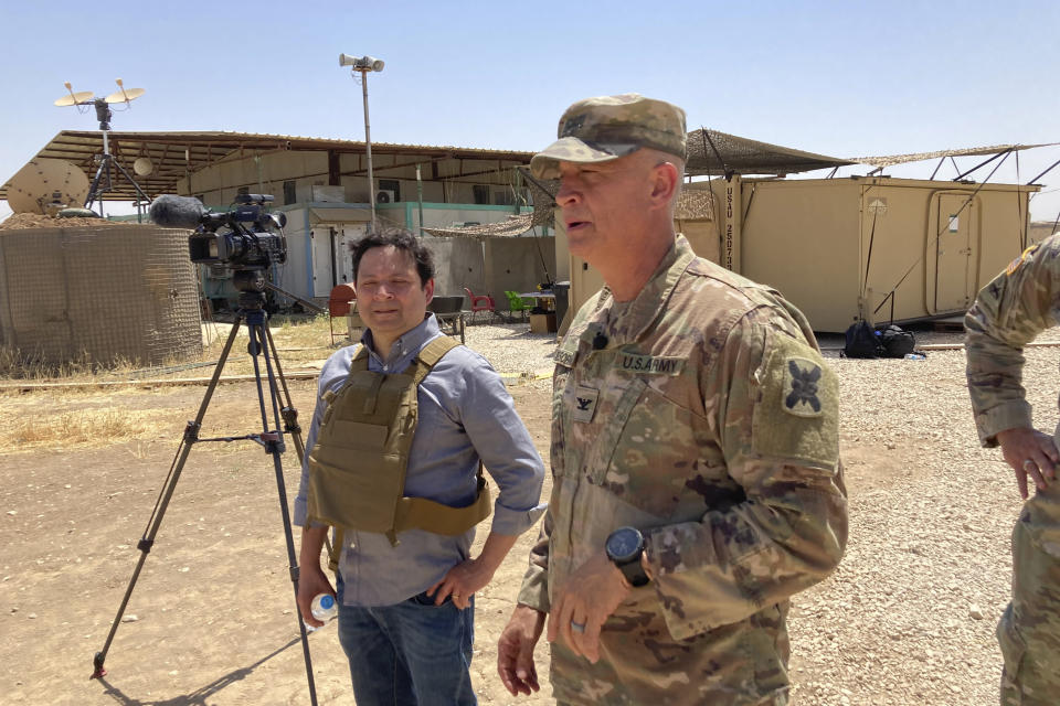 In this May 21, 2021, photo Col. Scott Desormeaux, who is with the Louisiana National Guard, talks to reporters in northern Syria during a visit by Marine Gen. Frank McKenzie, top U.S. commander for the Middle East. The Syria deployment is just one of many missions the Louisiana Guard had to juggle over the past year. Listening at left is ABC correspondent Luis Martinez. (AP Photo/Lolita Baldor)