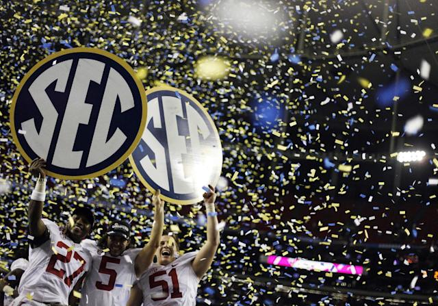 FILE - In this Dec. 1, 2012, file photo, Alabama players, from left, Nick Perry, Jeremy Shelley, and Carson Tinker celebrate after their 32-28 win in the Southeastern Conference championship NCAA college footbal game against Georgia, in Atlanta. The NCAA board of directors will vote Thursday, Aug. 7, 2014, on a proposal that would give the five wealthiest college football conferences the ability to make rules and pass legislation without the approval of the rest of Division I schools. (AP Photo/David Goldman, File)