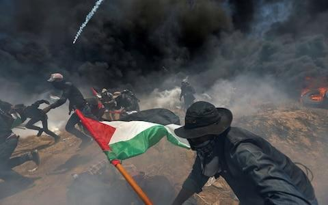 Palestinian demonstrators run for cover from Israeli fire and tear gas  - Credit: REUTERS