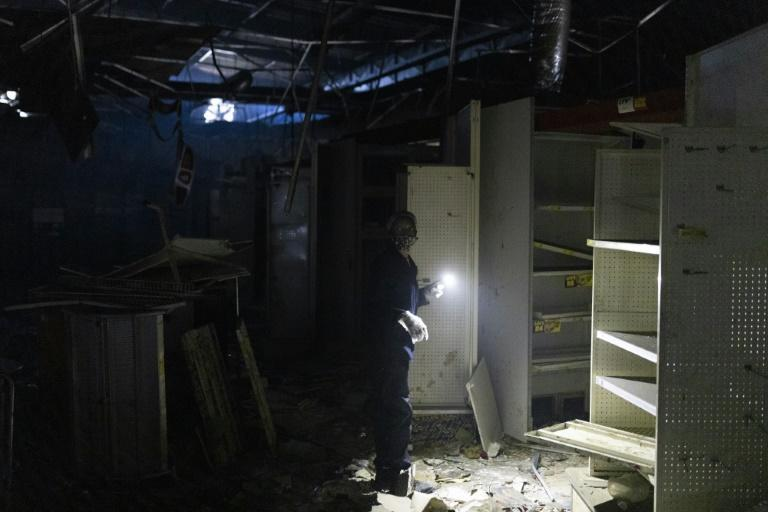 Aftermath: A woman uses a torch to clear debris at a looted shop in Durban's Dube Village Mall