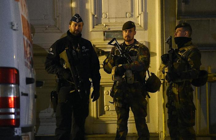 A Belgian policeman and two soldiers stand guard during a press conference by the country's prime minister concerning a security alert in Brussels on November 22, 2015 (AFP Photo/Emmanuel Dunand)
