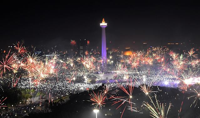 <p>Fireworks explode around National Monument during New Year celebration in Jakarta, Indonesia, January 1, 2018. (Photo: Wahyu Putro/Reuters) </p>
