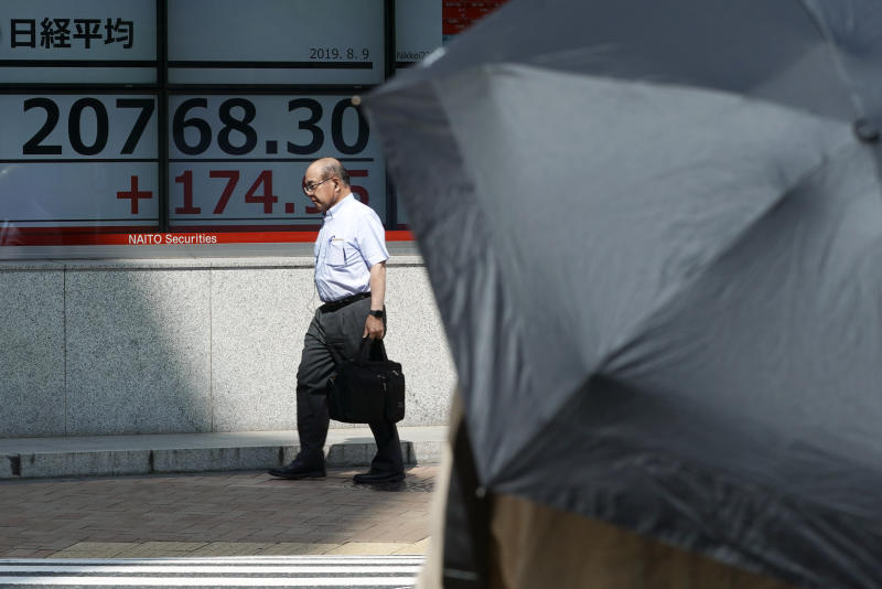 A man walks past an electronic stock board showing Japan's Nikkei 225 index at a securities firm in Tokyo Friday, Aug. 9, 2019. Asian shares rose Friday as investors bought back stocks following gains on Wall Street, although worries about a trade dispute between the U.S. and China remained.(AP Photo/Eugene Hoshiko)