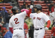 Boston Red Sox's Xander Bogaerts, left, welcomes home J.D. Martinez, right, after Martinez hit a homerun off a pitch by Seattle Mariners' Marco Gonzales during the first inning of a baseball game at Fenway Park, Sunday, May 12, 2019, in Boston. (AP Photo/Steven Senne)