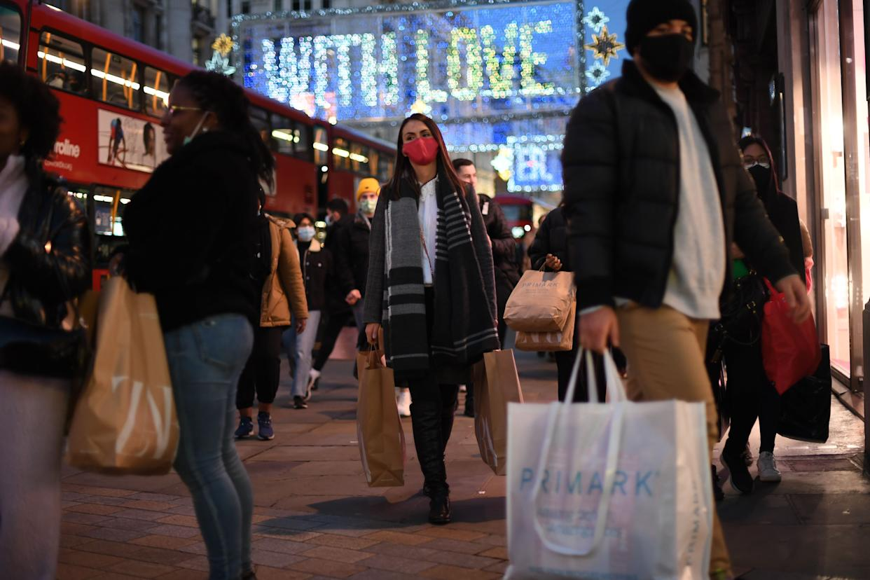 Shoppers, some wearing masks because of the coronavirus pandemic, walk along Regent Street in the main high-street shopping area of London on December 15, 2020 ahead of fresh measures for the capital amid rising infection rates. - The British capital faces tougher Covid-19 measures within days, the UK government said on December 14, with a new coronavirus variant emerging as a possible cause for rapidly rising infection rates. (Photo by DANIEL LEAL-OLIVAS / AFP) (Photo by DANIEL LEAL-OLIVAS/AFP via Getty Images)