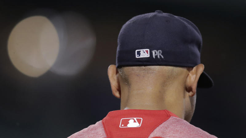 "Boston Red Sox manager Alex Cora's cap is embossed with the letters ""PR"", for his Puerto Rico homeland, during a baseball game at Fenway Park in Boston, Wednesday, July 17, 2019. (AP Photo/Charles Krupa)"