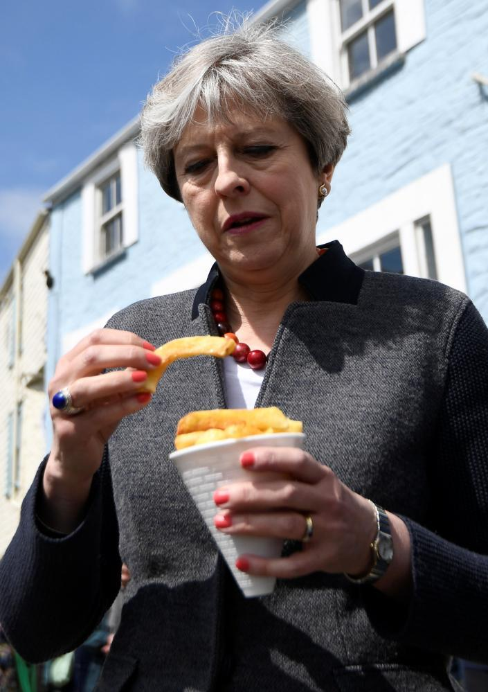 The prime minister of the United Kingdom looks suspiciously at a chip during her Cornwall visit.