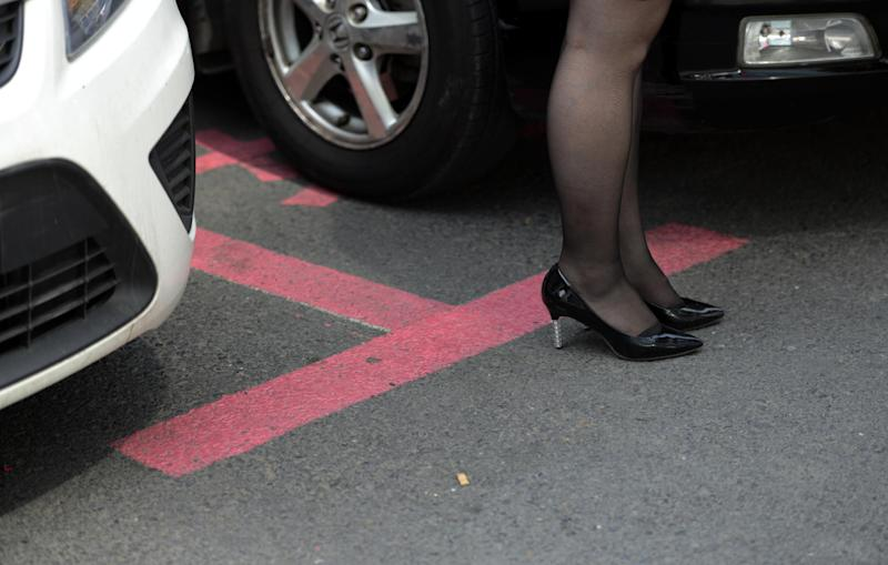A woman stands next to parking spaces marked out in pink in Dalian on July 7, 2014 (AFP Photo/Johannes Eisele)