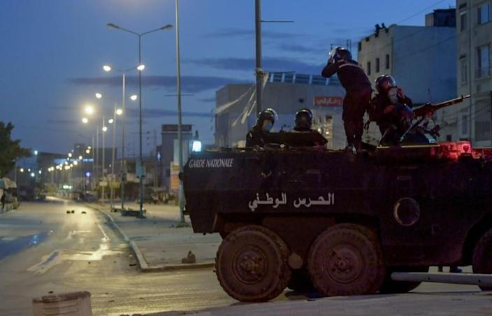 Tunisian National Guard troops on an armoured vehicle, stationed on a street amid clashes with demonstrators in the Ettadhamen neighbourhood in the capital Tunis on Sunday