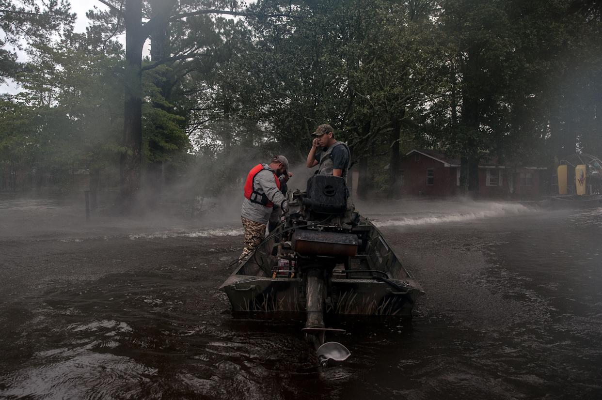 Rescuers with the Cajun Navy shield their faces from the spray off a fan boat as they prepare to enter a flooded neighborhood to evacuate people still in their homes in Lumberton on Sunday.
