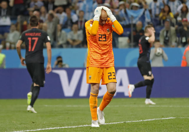 Argentina goalkeeper Wilfredo Caballero holds his head after Croatia's Ante Rebic, background right, scored the opening goal during the group D match between Argentina and Croatia at the 2018 soccer World Cup in Nizhny Novgorod Stadium in Nizhny Novgorod, Russia, Thursday, June 21, 2018. (AP Photo/Ricardo Mazalan)