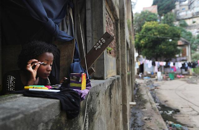 <p>Agatha, 13, who wants to become a model, applies makeup in the window of her family's home in the Mangueira favela, May 2, 2017, in Rio de Janeiro. (Photo: Mario Tama/Getty Images) </p>