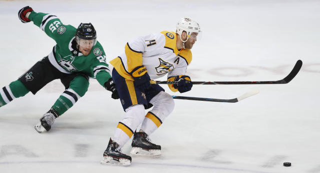 Nashville Predators defenseman Mattias Ekholm (14) is chased by Dallas Stars right wing Brett Ritchie (25) during the first period of an NHL hockey game in Dallas, Tuesday, Feb. 19, 2019. (AP Photo/LM Otero)
