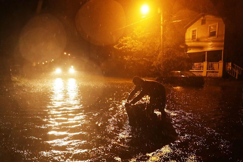 Michael Nelson floats in a boat made from a metal tub and fishing floats after the Neuse River went over its banks and flooded his street in New Bern on Thursday.