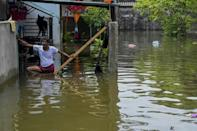 A resident stands in floodwaters after heavy monsoon rains in Kelaniya