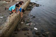 <p>Children try to catch a crab as they play on the polluted shore of Guanabara Bay in Rio de Janeiro, Brazil, Saturday, July 30, 2016. In Rio, the main tourist gateway to the country, a centuries-long sewage problem that was part of Brazil's colonial legacy has spiked in recent decades in tandem with the rural exodus that saw the metropolitan area nearly double in size since 1970. (AP Photo/Felipe Dana)</p>