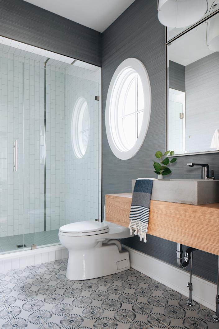 """<div class=""""caption""""> In the bathroom, a gray <a href=""""https://www.hollyhunt.com/"""" rel=""""nofollow noopener"""" target=""""_blank"""" data-ylk=""""slk:Holly Hunt"""" class=""""link rapid-noclick-resp"""">Holly Hunt</a> wall covering sets a serene scene against <a href=""""https://www.annsacks.com/"""" rel=""""nofollow noopener"""" target=""""_blank"""" data-ylk=""""slk:Ann Sacks"""" class=""""link rapid-noclick-resp"""">Ann Sacks</a> tiles. The mirror is from <a href=""""https://www.mirrorimagehome.com/"""" rel=""""nofollow noopener"""" target=""""_blank"""" data-ylk=""""slk:Mirror Image Home"""" class=""""link rapid-noclick-resp"""">Mirror Image Home</a>, and the bath towel is from <a href=""""https://amystormandco.com/"""" rel=""""nofollow noopener"""" target=""""_blank"""" data-ylk=""""slk:Amy Storm & Company"""" class=""""link rapid-noclick-resp"""">Amy Storm & Company</a>. </div>"""