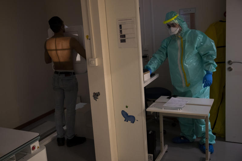 Medical staffer Wassim Kamari, who has symptoms of coronavirus, receives an x-ray of his lungs at the polyclinic Klinicare during a partial lockdown against the spread of Covid-19 in Brussels, Monday, April 6, 2020. The new coronavirus causes mild or moderate symptoms for most people, but for some, especially older adults and people with existing health problems, it can cause more severe illness or death. (AP Photo/Francisco Seco)
