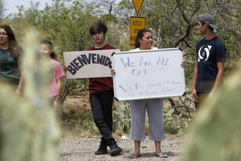 Martinez holds up sign as she and members of her family gather in support of undocumented immigrants in Oracle, Arizona
