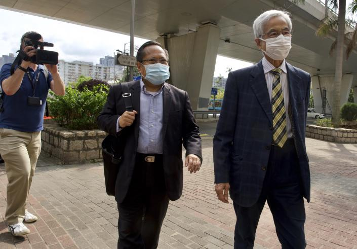 Pro-democracy lawmaker Martin Lee, center, and Albert Ho arrive at a court in Hong Kong Thursday, April 1, 2021. Seven pro-democracy advocates were convicted Thursday for organizing and participating in an unlawful assembly during massive anti-government protests in 2019, as Hong Kong continues its crackdown on dissent. (AP Photo/Vincent Yu)
